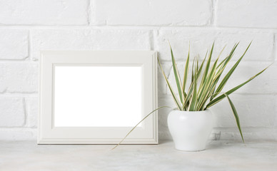 White wooden frame with copyspace and greenery on white Brick wall background.