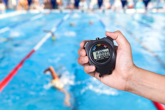 Stopwatch holding on hand with competitions of swimming background.