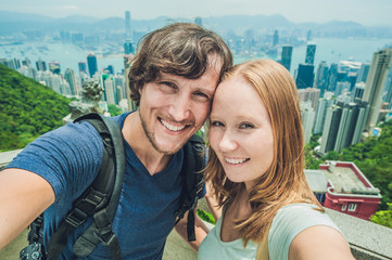 Caucasian couple in Hong Kong. Young people taking selfie picture at viewpoint of famous attraction Victoria Peak, HK, China