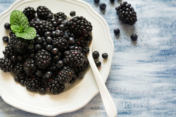 Plate with blackberries and blueberries on blue wooden background. Top view