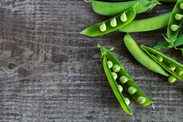 young juicy green peas on a wooden table. copy space