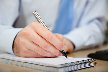 Office worker writing in notebook
