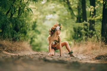 Beautiful little girl in image of nymph dryad sits in forest road.