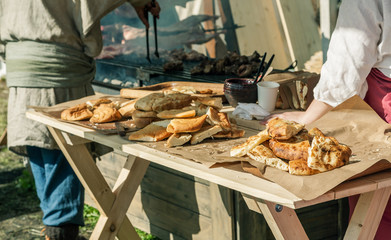 Sliced pita bread on a wooden table in warm summer sunlight, outdoors cooking, selective focus