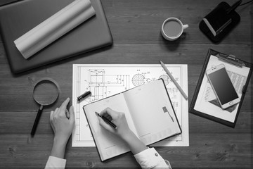 Girl is sitting at table with business accessories, cup of coffee and a laptop, works with drawings, graphs, tables, write in diary. Top view.