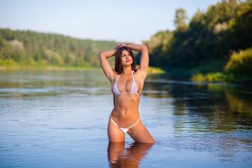 Wet amazing woman in bikini. beautiful girl in a bikini in water. Fitness model posing on the shore