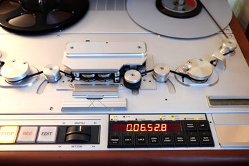 Modern professional studio reel to reel stereo tape recorder with magnetic tape front view close up
