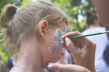 little girl getting her face painted like a butterfly by face painting artist.