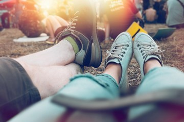 Legs of young people at summer music festival. Relaxing fun time sitting on the grass in front of stage. Sunlight