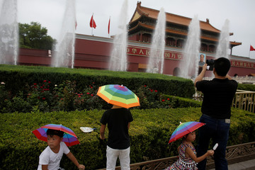 A man takes pictures as children wear umbrella shaped sun hats at Tiananmen Square in Beijing