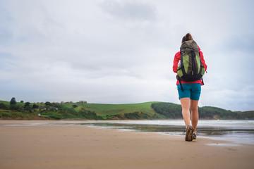 Backpacker girl traveler walk on deserted ocen beach