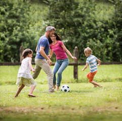 Cheerful family playing football in a garden
