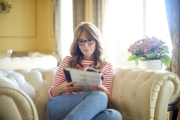 Relaxing woman portrait. Shot of a beautiful middle aged woman reading a magazine while relaxing on armchair in her luxury home.