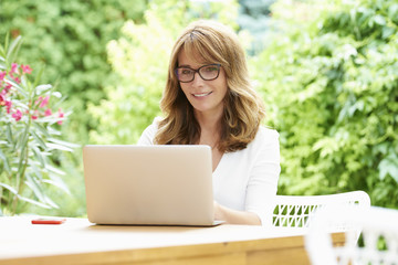 Woman with laptop outdoor. Portrait of a beautiful middle aged woman using laptop while sitting in balcony at home.