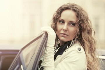 Sad beautiful fashion woman with long curly hairs next to her car