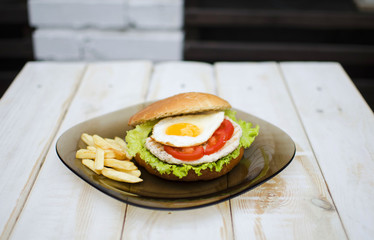 Hamburger with fresh lettuce and eggs. French fry