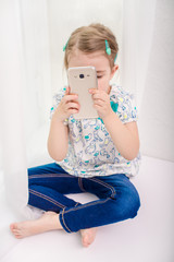 Little girl child is taking photo or video with mobile phone camera