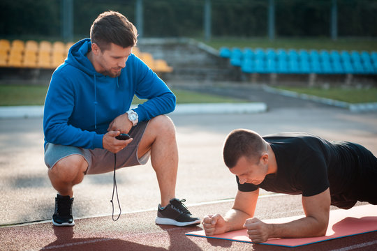 morning plank exercises with personal coach with stopwatch;
