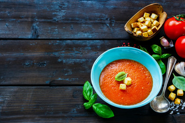 Freshly made Gazpacho Tomato summer cream soup in bowl and basil on wooden background. Selective focus, copy space.