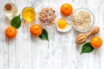 Sweet summer breakfast. Oatmeal, oranges, honey, sugar on wooden table background top view copyspace