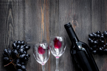 Wine glasses and bottle on dark wooden table background top view copyspace