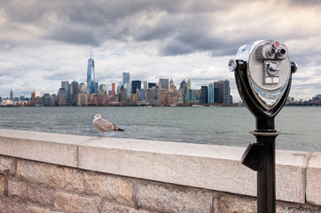 Binoculars on Ellis Island pointed towards Manhattan's skyline in a cloudy day