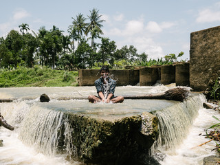 Indian man playing with water under dam