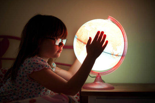 Side view of a girl holding illuminated globe