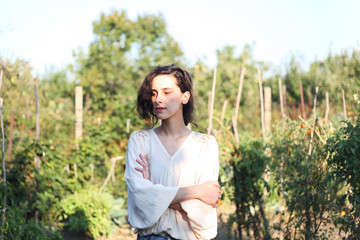 Portrait of a young woman standing in the garden during a sunny day