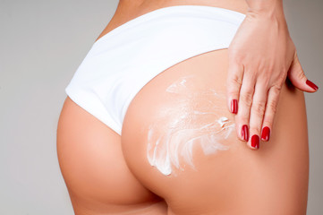Body care. Woman applying cream on legs and buttocks from cellulite