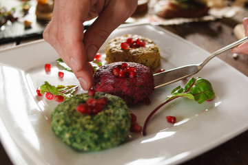 Paste balls of national georgian cuisine in restaurant. Close up process of decoration delicious soft appetizers with pomegranate seeds on white plate
