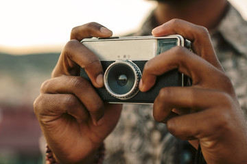 Closeup of a young black man holding an old camera outdoors.