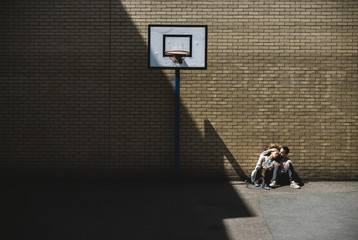 Young couple sitting in a basketball court