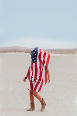 Walking Woman Covered by a American Flag in the Desert