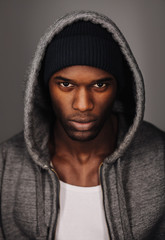 Black man in urban style looking tough on grey background
