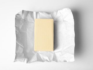Wrapping with piece of butter on white background