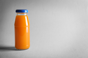 Delicious juice in bottle on light background