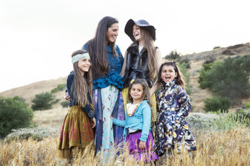Mother and four daughters laughing and smiling surrounded by nature