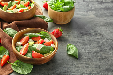 Bowls of salad with spinach leaves, strawberry and cheese on table