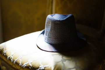 elegant and stylish men's gray hat lies on a yellow armchair