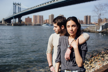 Young couple walking along the river in Brooklyn in a sunny day