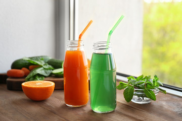 Delicious juices in bottles and fruits on window sill