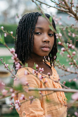 African American girl next to peach flowers