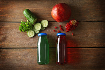 Delicious juices in bottles and ingredients on wooden background