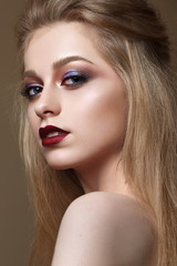 Portrait of beautiful blondy girl with professional color makeup, perfect skin. Trendy colorful smoky eyes. Evening makeup with red lips