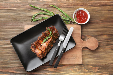 Plate with delicious pork ribs and rosemary on wooden table