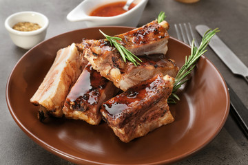 Plate with delicious pork ribs and rosemary on table, closeup