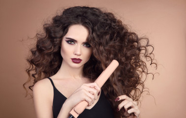 Hairstyling. Curly Beauty hair. Glamour portrait of beautiful woman model holding straightening iron. Brunette with marsala matte lips and long hairstyle isolated on beige background