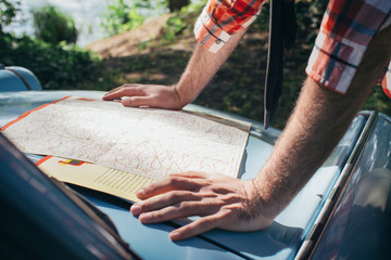 Close Up of Young Man Looking at Road Map on Car Hood