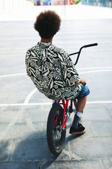 Back view of a young african american boy with his BMX bike in a skate park.